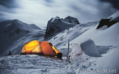 Illuminated tent of winter camp in the mountains