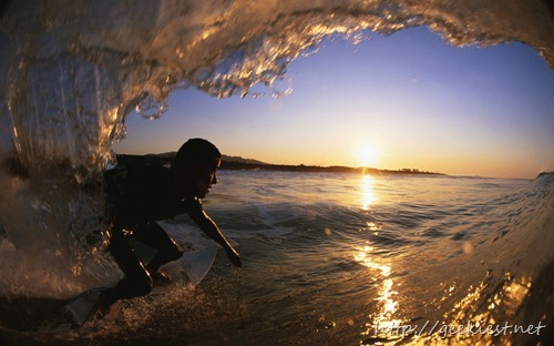 Male surfer riding ocean curl
